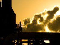 At sunrise a worker performs maintainance at a California steam energy plant.